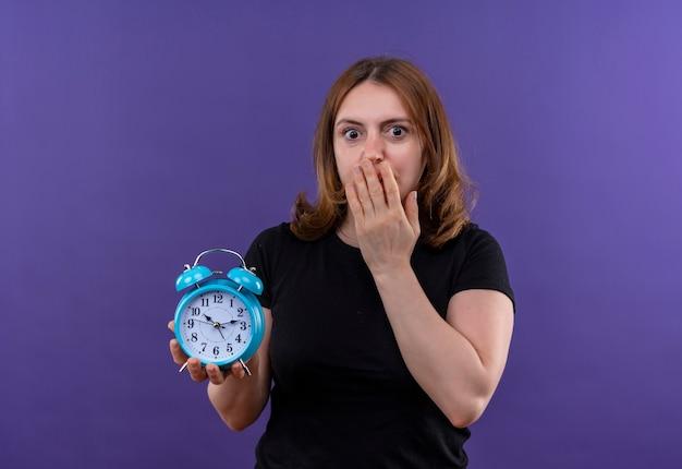Mulher jovem e casual surpresa segurando o despertador com a mão na boca na parede roxa isolada com espaço de cópia