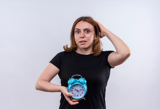 Mulher jovem e casual surpresa segurando o despertador e colocando a mão na cabeça em uma parede branca isolada com espaço de cópia