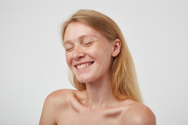 Mulher jovem e charmosa de aparência agradável, com cabelo comprido de raposa, mantendo os olhos fechados enquanto sorri feliz, estando de bom humor enquanto posa sobre uma parede branca