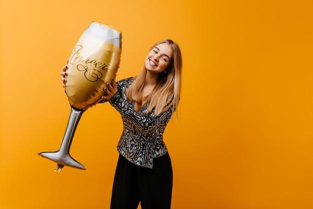 Mulher jovem e charmosa em uma jaqueta brilhante segurando um copo de vinho. retrato interior de mulher cega entusiasmada e relaxante durante o evento.