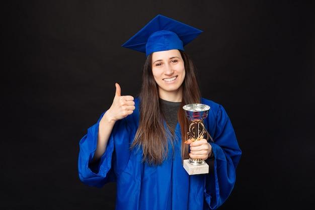 Mulher jovem e charmosa estudante vestindo solteiro, mostrando o polegar e segurando uma taça de campeão