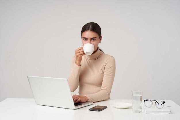 Mulher jovem e charmosa morena de olhos azuis em poloneck bege, bebendo café enquanto digita um texto no teclado, olhando positivamente enquanto está sentada na parede branca