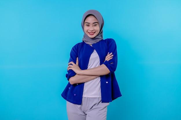 Mulher jovem e charmosa otimista com um sorriso fofo e um sorriso branco sobre fundo azul claro.
