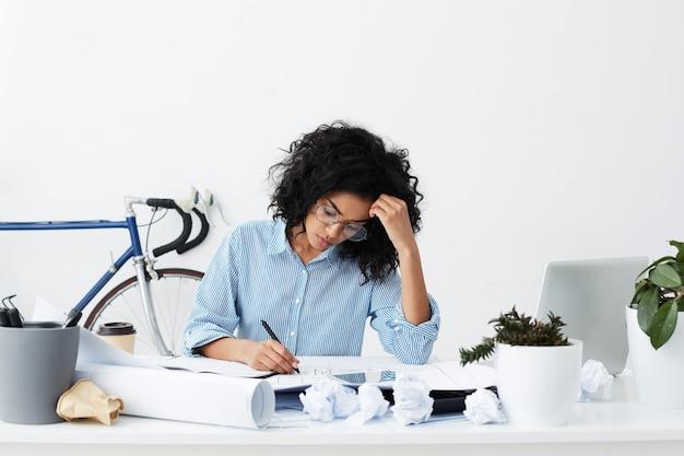 Mulher jovem e concentrada de pele escura usando óculos e camisa azul, sentada no local de trabalho