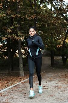 Mulher jovem e concentrada em fitness correndo no parque, ouvindo música com fones de ouvido
