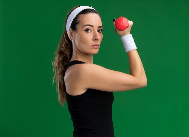Mulher jovem e confiante, bonita e esportiva, usando fita para a cabeça e pulseiras, em pé, segurando um haltere de perfil