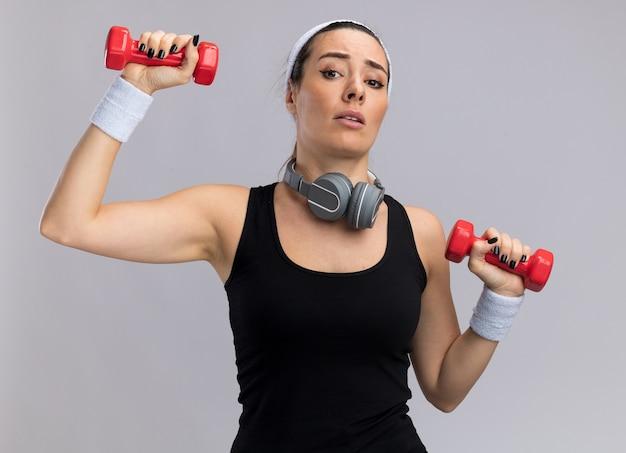 Mulher jovem e confiante, bonita e esportiva, usando fita para a cabeça e pulseiras levantando halteres com fones de ouvido ao redor do pescoço, olhando para a frente, isolado na parede branca