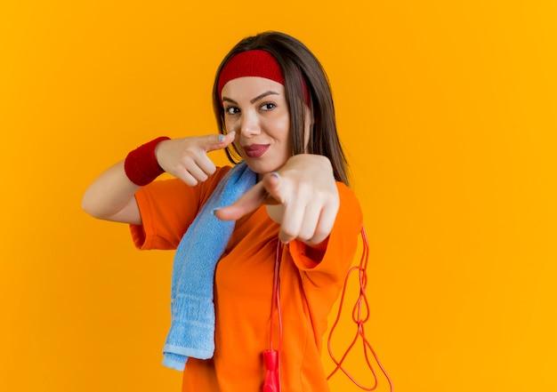 Mulher jovem e confiante e esportiva usando fita para a cabeça e pulseiras, vista de perfil e toalha