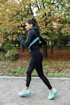 Mulher jovem e confiante em fitness correndo no parque, ouvindo música com fones de ouvido