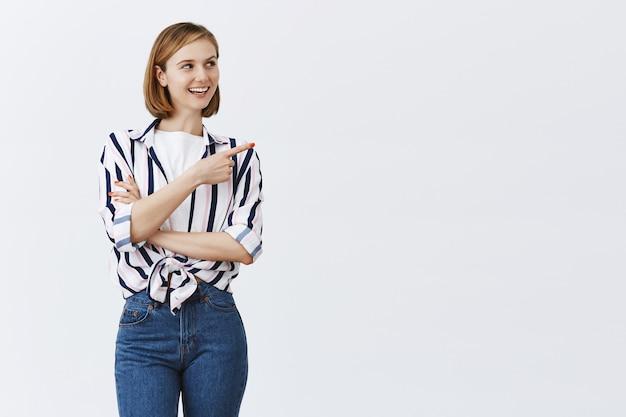 Mulher jovem e confiante sorridente apontando o canto superior direito para copyspace