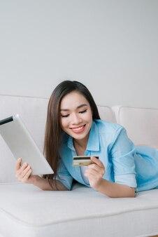 Mulher jovem e confiante trabalhando com tablet digital e cartão de crédito em casa
