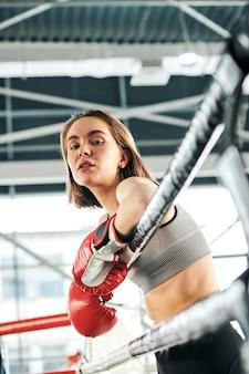 Mulher jovem e confiante usando roupas esportivas e luvas de boxe, ao lado das grades do rinque, enquanto aproveita o intervalo entre os treinos na academia