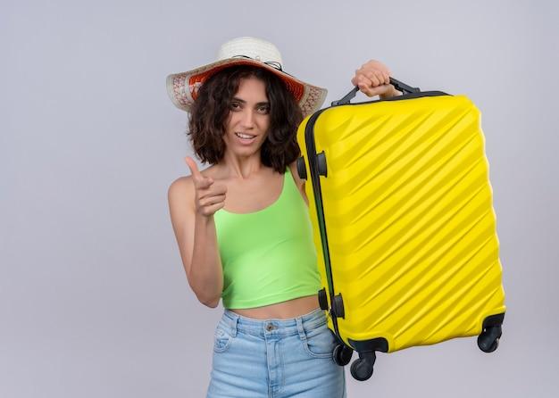 Mulher jovem e confiante viajante bonita usando chapéu, levantando a mala e apontando na parede branca isolada com espaço de cópia
