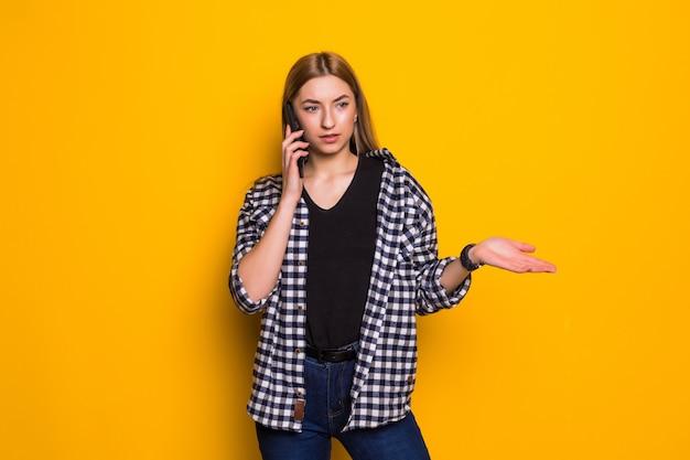 Mulher jovem e confusa com excesso de peso em pé, isolada na parede amarela, falando no celular
