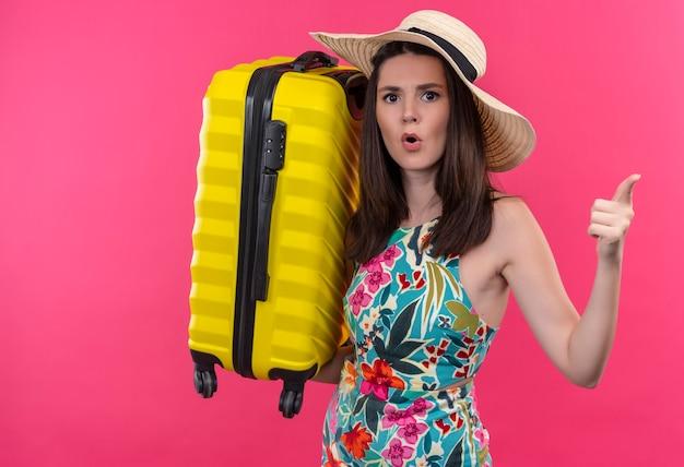 Mulher jovem e confusa com um chapéu segurando uma mala na parede rosa isolada