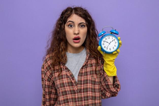 Mulher jovem e confusa da limpeza usando luvas segurando um despertador