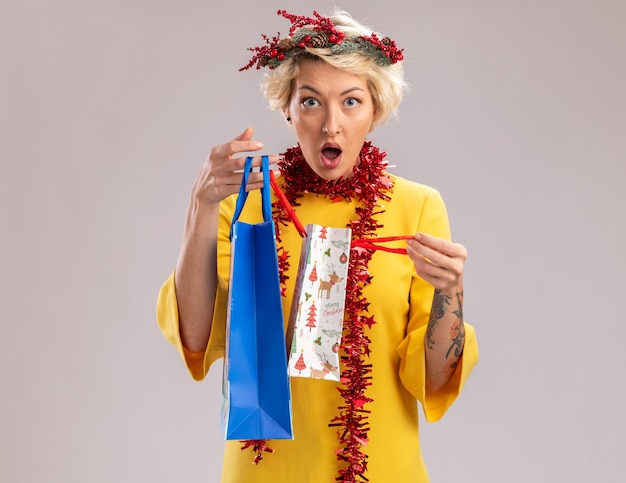 Mulher jovem e curiosa com coroa de flores de natal e guirlanda de ouropel em volta do pescoço segurando sacolas de presente de natal, abrindo uma delas olhando para a câmera, isolada no fundo branco
