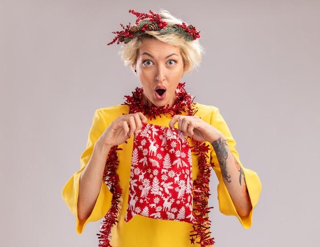 Mulher jovem e curiosa com coroa de flores de natal e guirlanda de ouropel em volta do pescoço segurando um saco de presente de natal, abrindo-o e olhando para a câmera