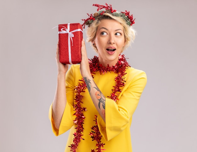 Mulher jovem e curiosa com coroa de flores de natal e guirlanda de ouropel no pescoço segurando um pacote de presente de natal perto da cabeça, olhando para ele isolado no fundo branco