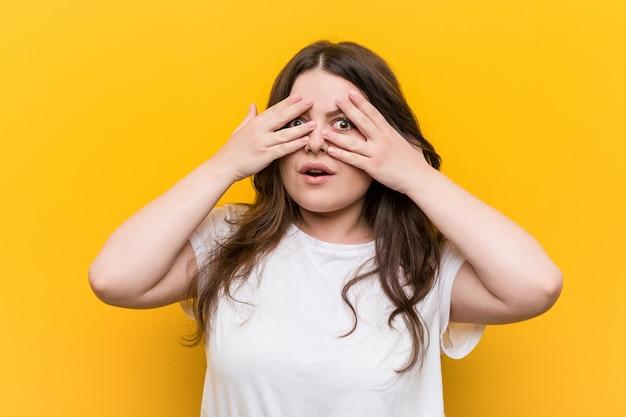 Mulher jovem e curvilínea plus size pisca entre os dedos, assustada e nervosa.