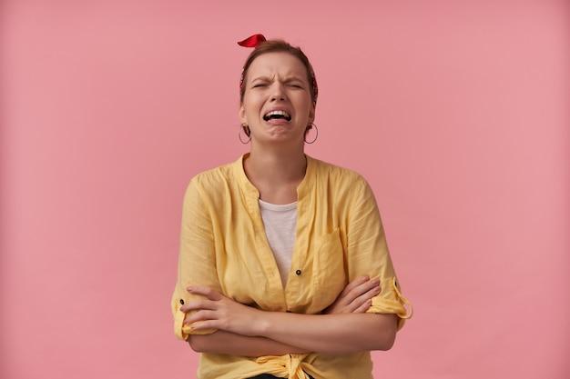 Mulher jovem e desesperada, com uma camisa amarela e uma faixa na cabeça com as mãos cruzadas, gritando e chorando sobre a parede rosa