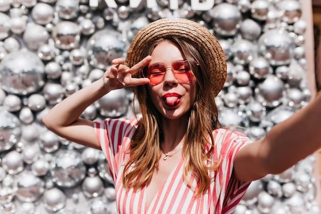 Mulher jovem e deslumbrante em óculos de sol rosa, fazendo selfie. garota alegre com chapéu de palha, posando com a língua de fora, perto de bolas de discoteca.