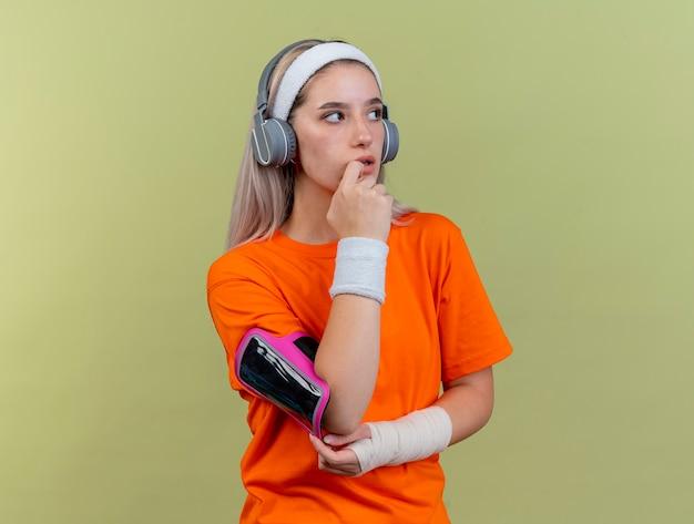 Mulher jovem e desportiva confusa com aparelho nos fones de ouvido, pulseira de tiara e braçadeira de telefone coloca a mão no queixo olhando para o lado isolado na parede verde oliva