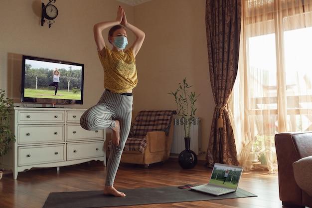 Mulher jovem e desportiva fazendo aulas de ioga online e praticando em casa enquanto está em quarentena. conceito de estilo de vida saudável, bem-estar, segurança durante a pandemia de coronavírus, à procura de um novo hobby.