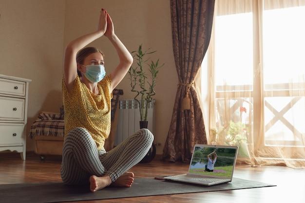 Mulher jovem e desportiva fazendo aulas de ioga online e praticando em casa enquanto está em quarentena.