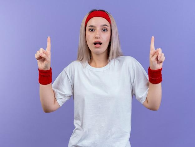 Mulher jovem e desportiva impressionada com aparelho usando fita para a cabeça e pulseiras apontando para cima com as duas mãos isoladas na parede roxa