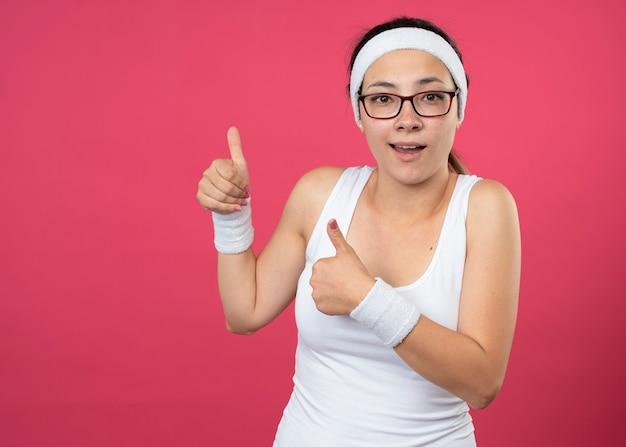 Mulher jovem e desportiva impressionada com óculos ópticos, fita para a cabeça e pulseiras com o polegar para cima de duas mãos isoladas na parede rosa