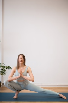 Mulher jovem e desportiva praticando ioga na parede branca com plantas - conceito de vida saudável e equilíbrio natural entre o corpo e o desenvolvimento mental