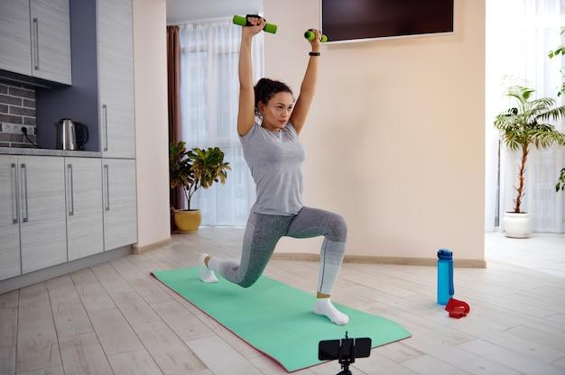 Mulher jovem e desportiva segurando halteres e erguendo os braços enquanto faz exercícios de estocadas em uma esteira de ginástica em frente ao celular em casa
