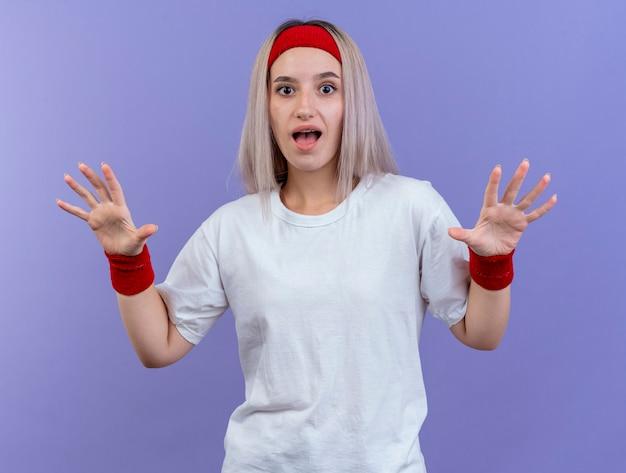 Mulher jovem e desportiva surpreendida com suspensórios, bandana e pulseiras com as mãos abertas, isoladas na parede roxa