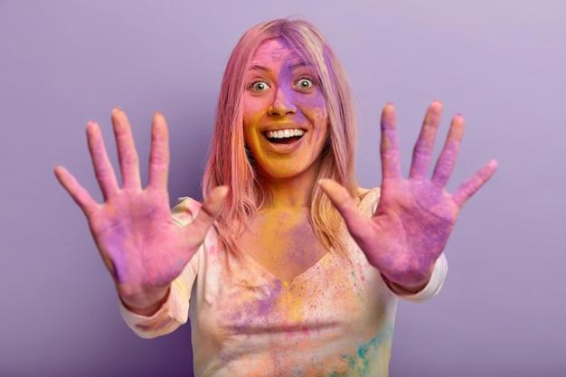 Mulher jovem e divertida satisfeita estende ambas as palmas das mãos manchadas com pó seco colorido, expressão facial feliz, se diverte com os amigos durante o festival holi, isolado contra a parede roxa.