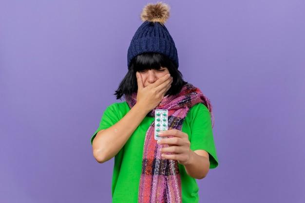 Mulher jovem e doente, caucasiana, dolorida, com chapéu e lenço de inverno, segurando um pacote de cápsulas médicas, mantendo a mão na boca, sofrendo de dor de dente, com os olhos fechados isolados