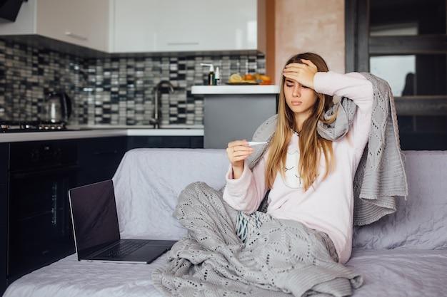 Mulher jovem e doente, caucasiana, em casa cinza, usar sentado na cama com um laptop trabalhando