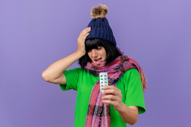Mulher jovem e doente com dor e chapéu de inverno e lenço segurando um pacote de cápsulas segurando a mão na cabeça, sofrendo de dor de cabeça com os olhos fechados, isolado na parede roxa com espaço de cópia