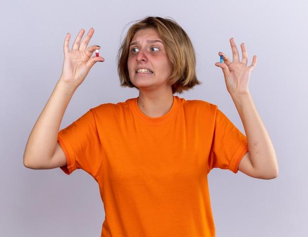 Mulher jovem e doente com uma camiseta laranja se sentindo mal, sofrendo de gripe, segurando comprimidos nas mãos, parecendo confusa e preocupada em pé sobre uma parede branca
