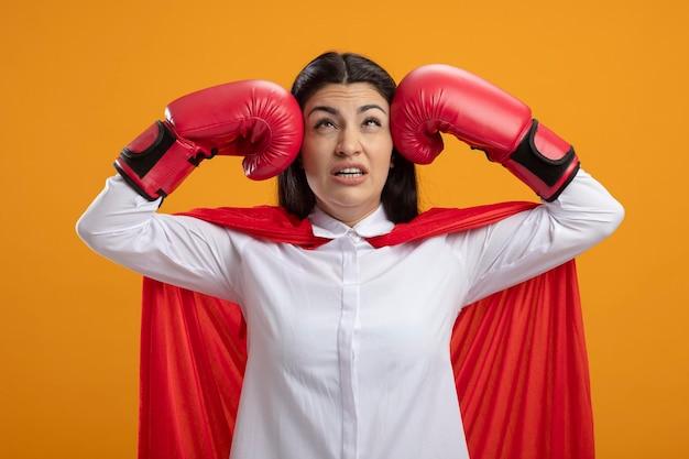 Mulher jovem e dolorida de super-heroína usando luvas de caixa e batendo na cabeça, olhando para cima, isolada na parede laranja