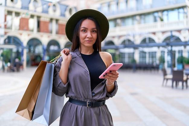 Mulher jovem e elegante, atraente hippie, viciada em compras com sacolas de papel