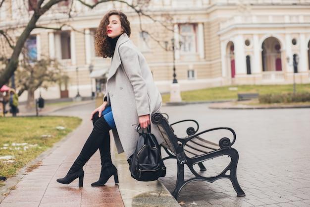 Mulher jovem e elegante caminhando na cidade de outono, estação fria, usando botas pretas de salto alto, mochila de couro, acessórios, casaco cinza, sentada no banco, tendência da moda