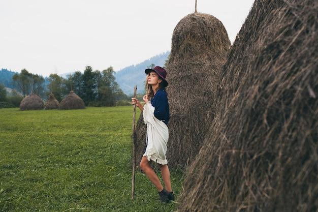 Mulher jovem e elegante caminhando no campo na paisagem de montanhas e campos verdes com roupa de outono