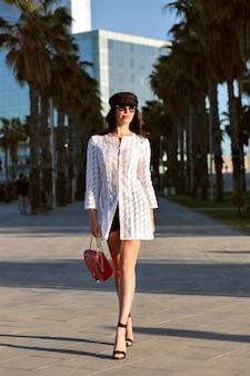 Mulher jovem e elegante caminhando sozinha, roupas e acessórios elegantes da moda, senhora sexy de meia-idade, cores enfraquecidas, becos de palmas.