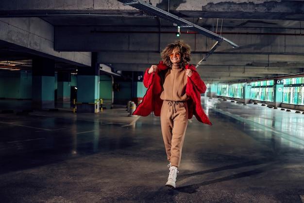 Mulher jovem e elegante com cabelo encaracolado, segurando a mão no bolso da jaqueta e andando na garagem subterrânea
