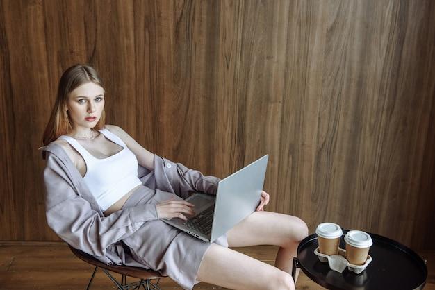 Mulher jovem e elegante com um laptop sentado