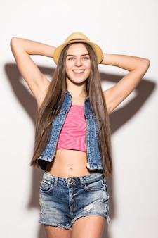 Mulher jovem e elegante com um top roxo na moda de manga longa, shorts brancos, óculos de sol pretos, chapéu de palha e colar de pérolas