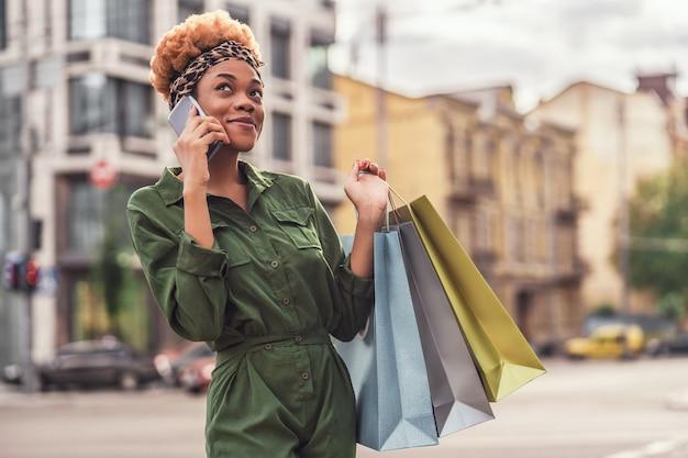 Mulher jovem e elegante em pé na rua enquanto segura muitas sacolas de compras e fala no smartphone