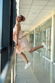 Mulher jovem e elegante em um vestido rosa posando dentro de um longo corredor