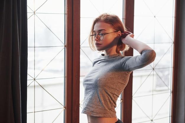 Mulher jovem e elegante. garota loira sexy de óculos, roupas íntimas e sem sutiã debaixo da camisa posando perto da janela na sala